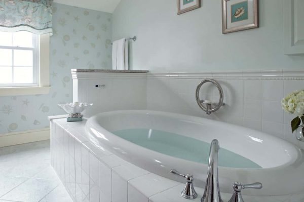 Large oval white tub surrounded by white tile, light blueish-green walls, white tiled floors and sunny window