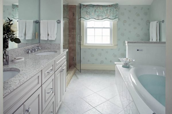 Beautiful bathroom with white tiled floor, white vanity, white tub, sunny window and dual sink top