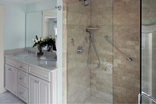 Beautiful bathroom with white vanity, dual sink top, large mirror, fresh flowers and walk-in tiled shower with glass door