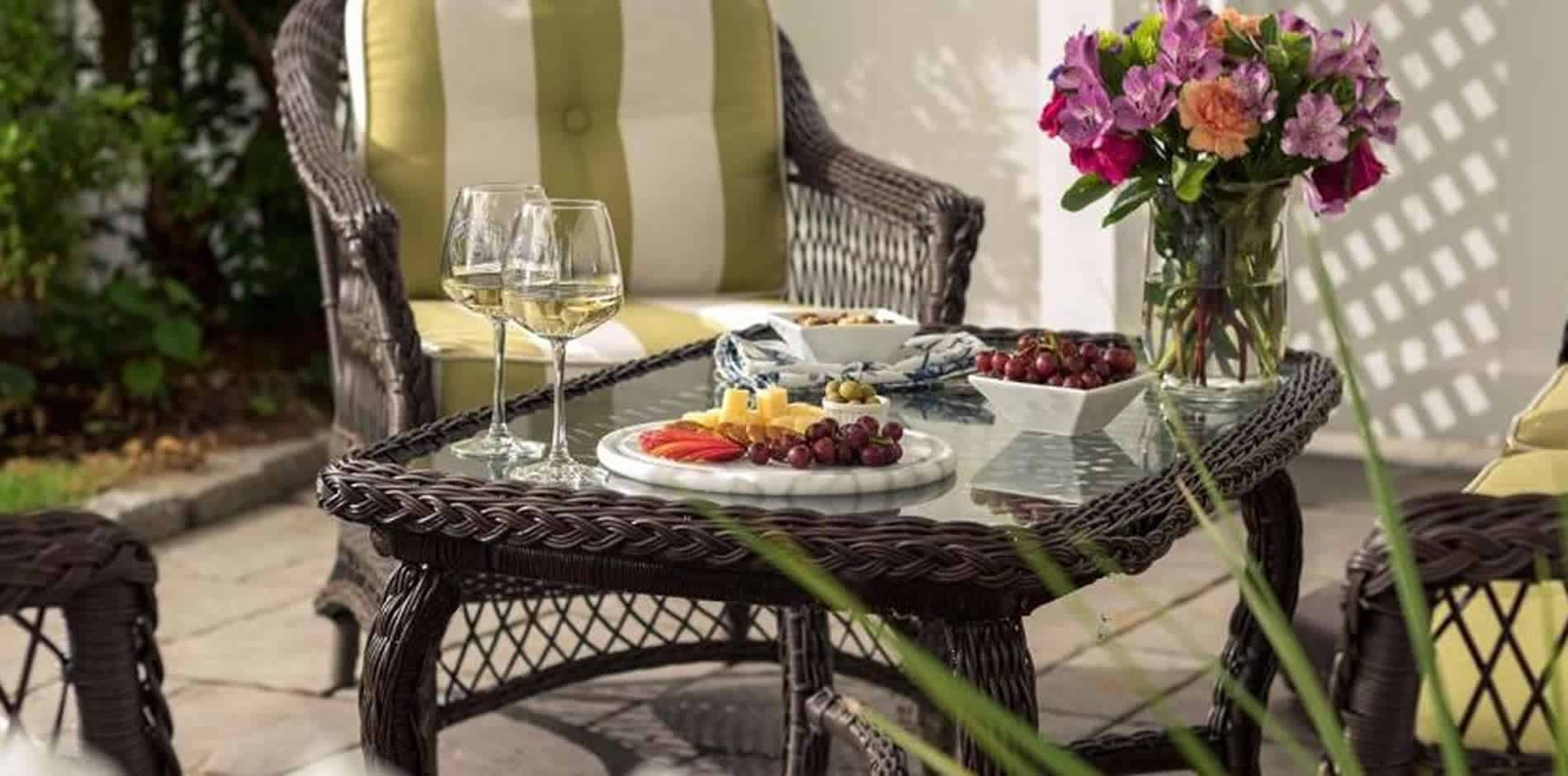 Wicker patio furniture, plates of grapes and cheese, white wine glasses and fresh flowers