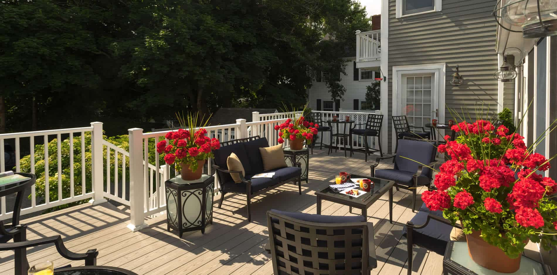 Spacious deck with white railing, dark patio furniture and pots of red flowers