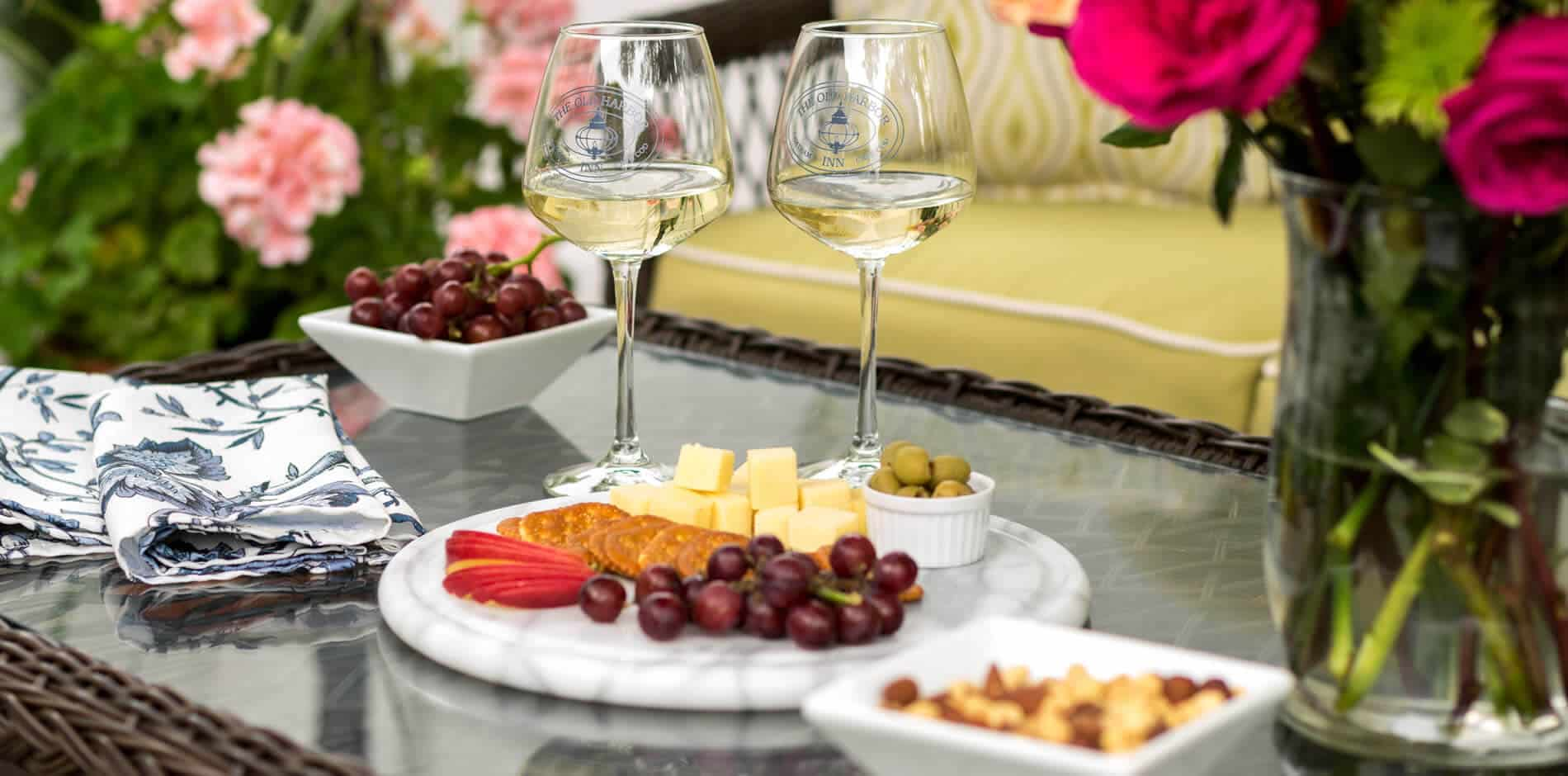 Wicker and glass patio table topped with fresh flowers, white wine, and marble tray topped with cheese and grapes