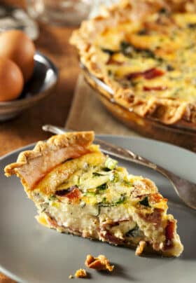 Plate topped with a slice of bacon and vegetable quiche