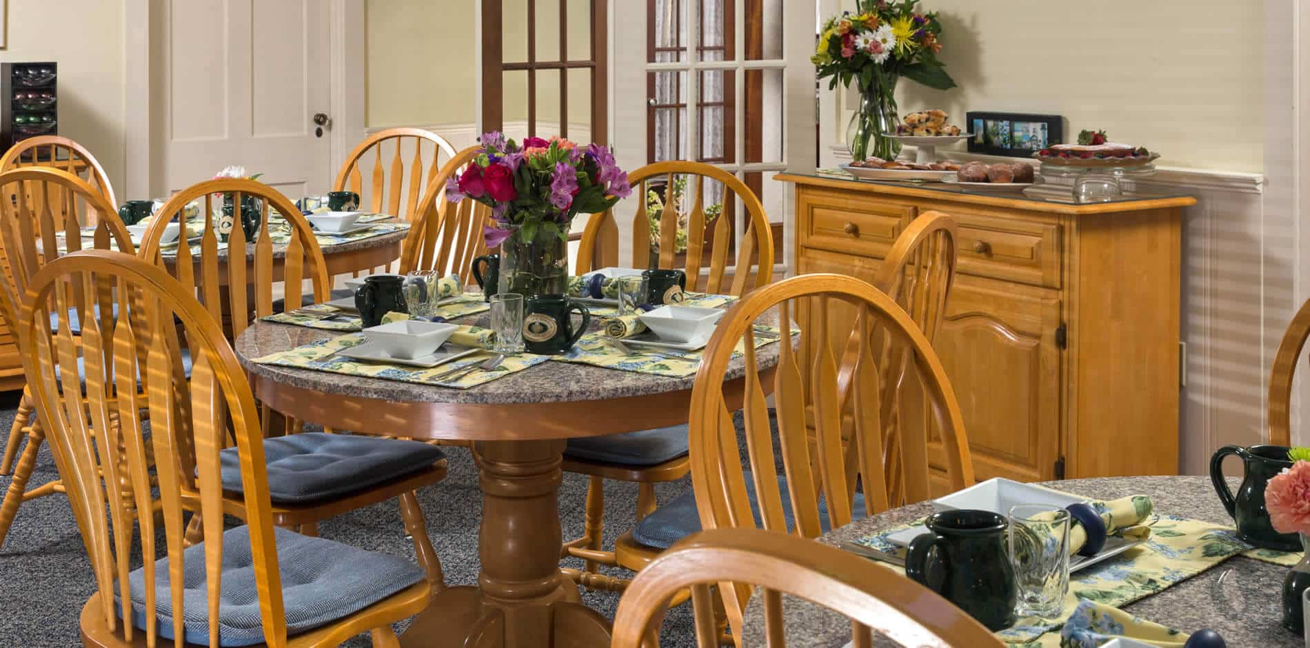 Sunny dining room with round tables and chairs set for a meal and fresh flowers