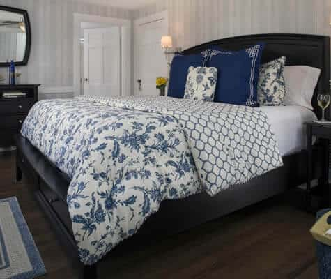 Beautiful guest room with wood floors and dark brown sleigh bed topped with blue and white bedding