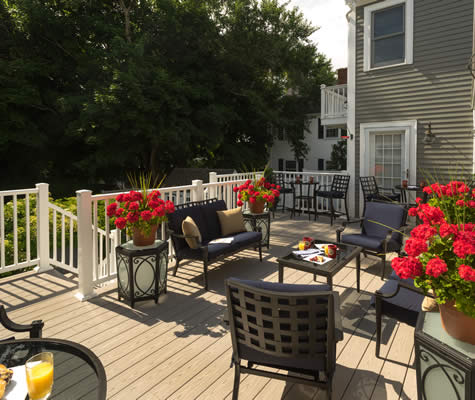 Spacious deck with white railing, assorted black patio furniture, pots of red flowers amidst dark green trees