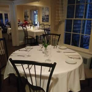 Elegant country style restaurant with white cloth topped tables and dark stained chairs