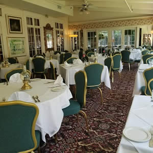 Elegant nautical restaurant dining room with white cloth topped tables and green and gold chairs
