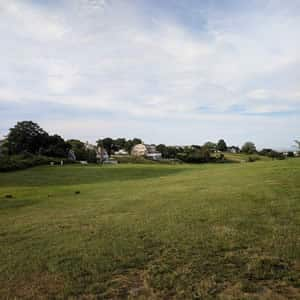 Rolling golf course terrain amidst blue skies with soft white clouds
