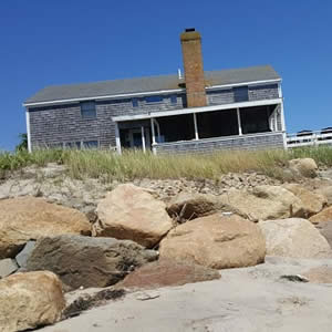 Weathered wood house at the top of a small dune with boulders and beach grass and blue skies