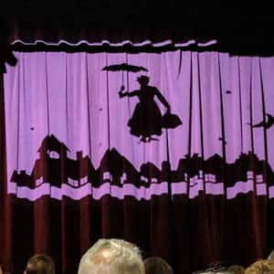 Pink and burgundy theater stage screen with the silhouette of Mary Poppins holding an umbrella in the sky over houses
