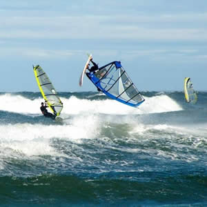 Three windsurfers in the ocean - two yellow and one blue - surfing white capped waves