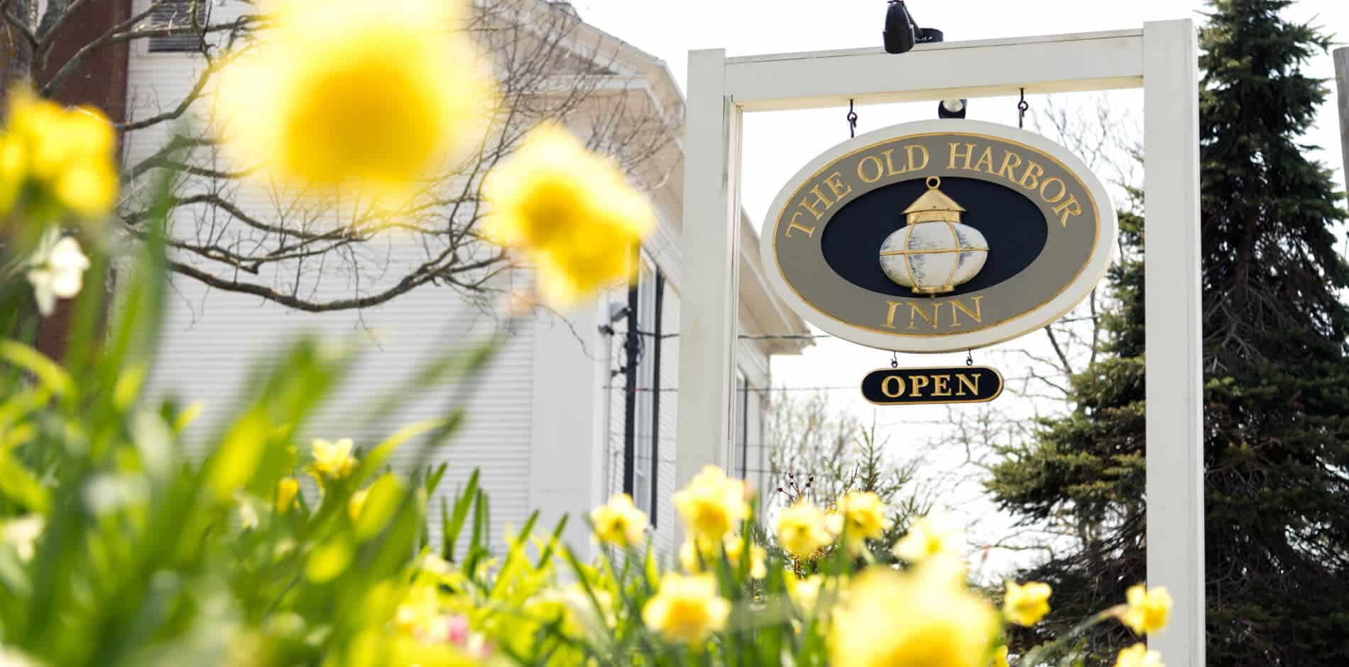 Large outdoor sign with hanging oval sign trimmed in gold that says The Old Harbor Inn Open