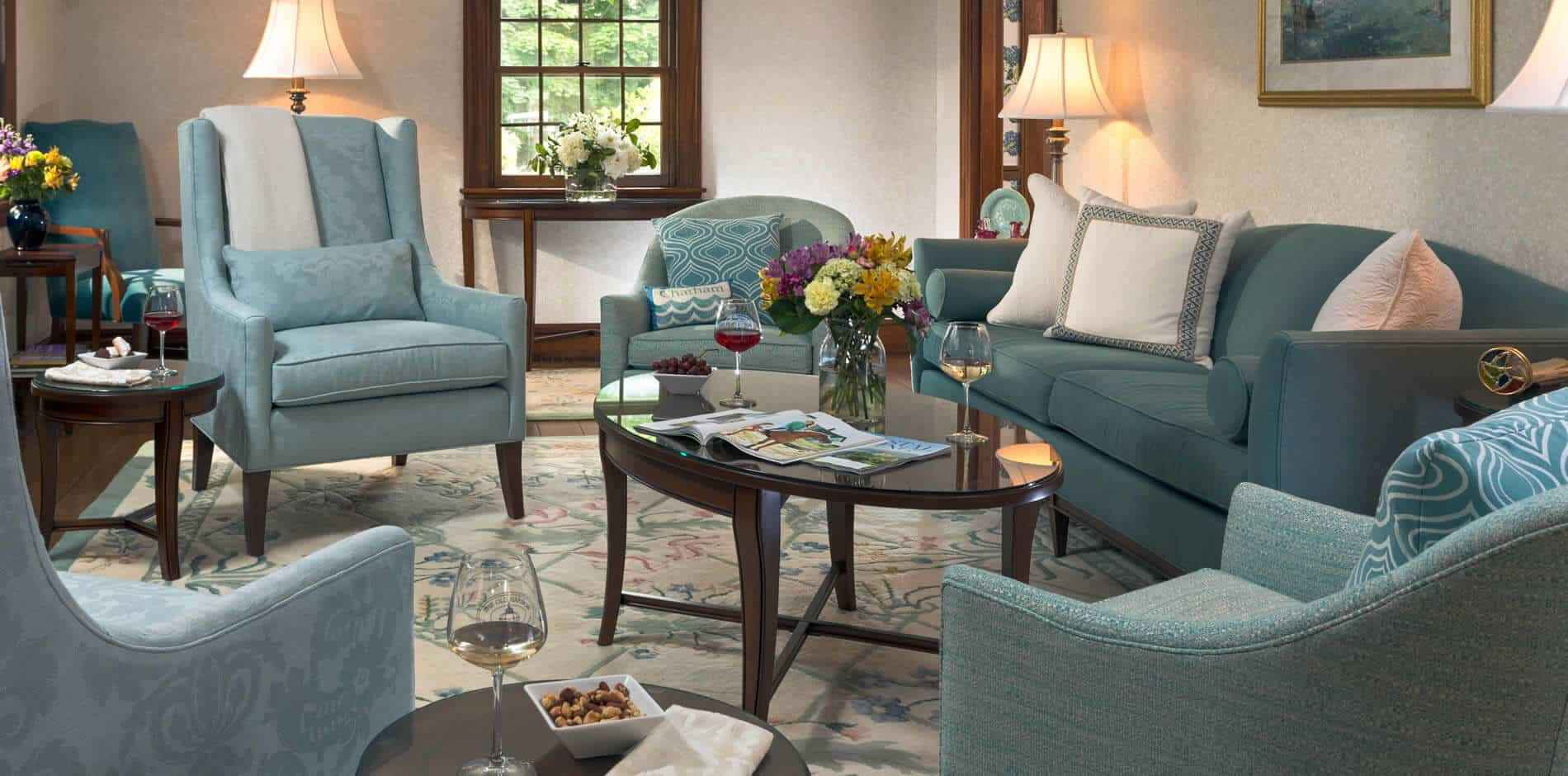 Beige living room with wood trim, light blue upholstered furniture, several tables with wine glasses