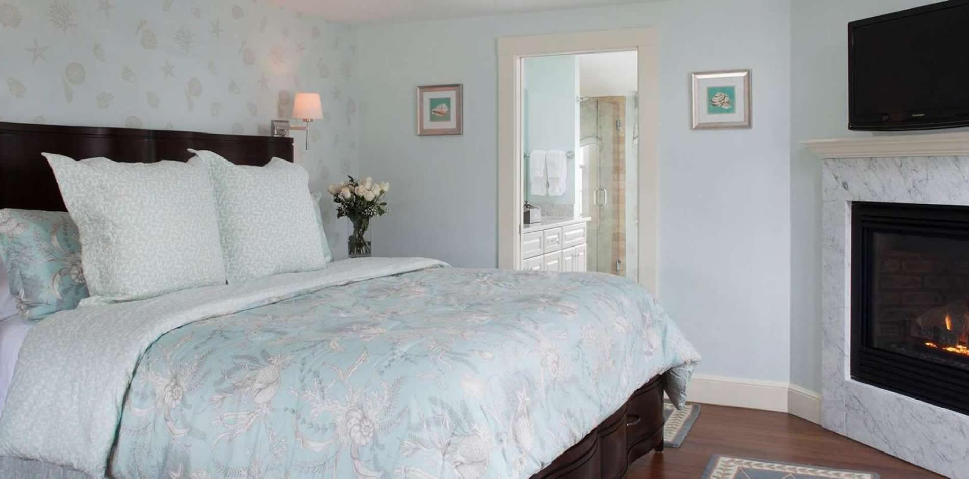 Light blue guest room with wood floor, bed topped with soft floral bedding, corner gas fireplace and tv