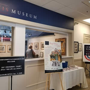 Blue and white museum entrance with signs, posters, and a display table