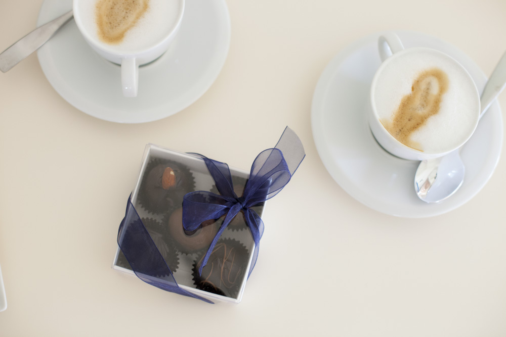 Two white cups on saucers filled with cappuccino next to a box of five decadent chocolates