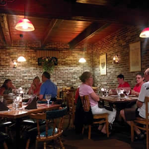 Diners eating in a casual, rustic restaurant with brick walls and wood ceilings