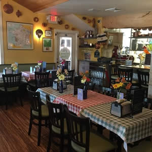 Country style restaurant with dark wood tables and chairs and checkered table cloths