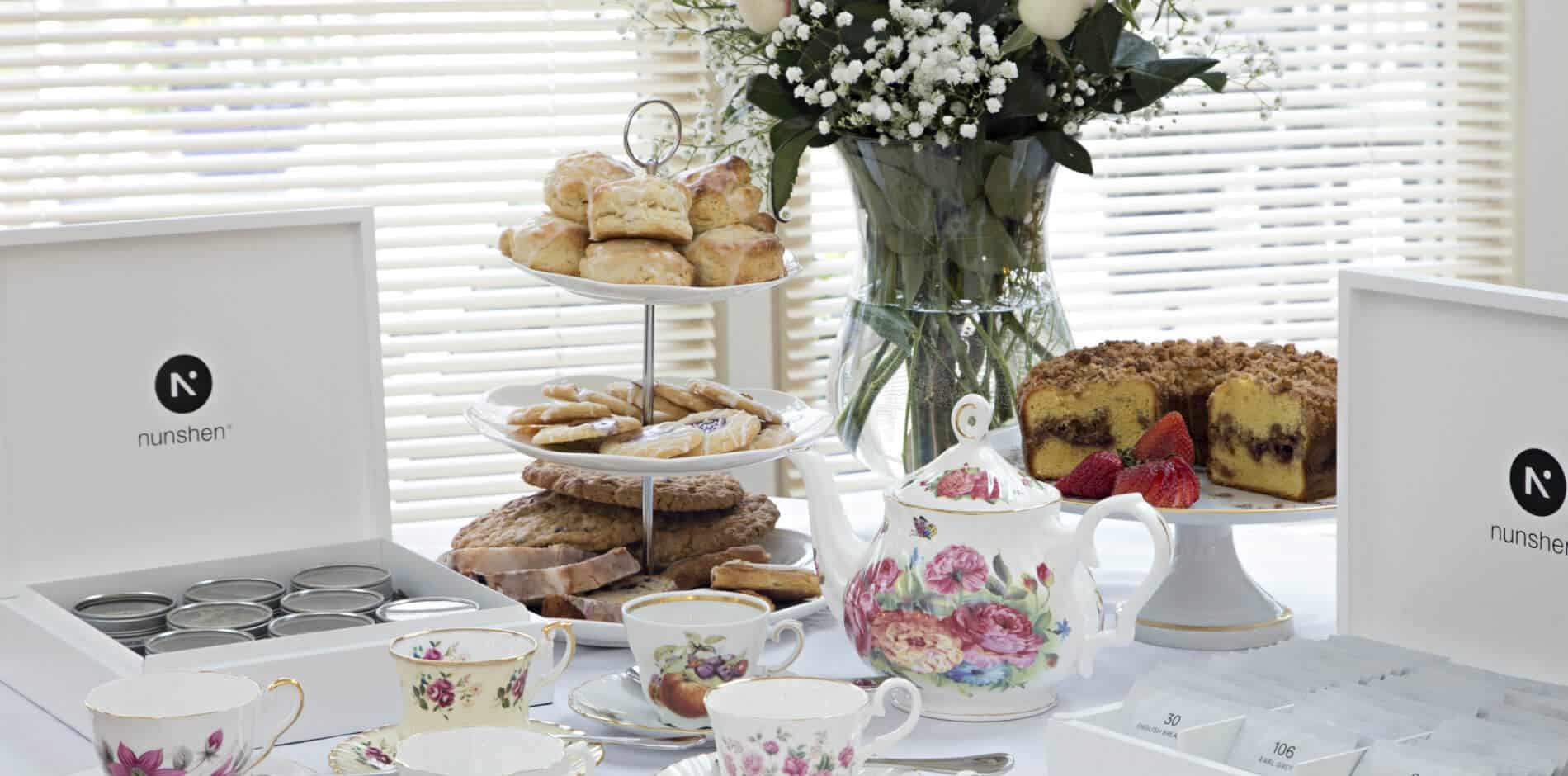Display of teas in white tea boxes, with fine china cups, saucers and tea pot in front of cinnamon crumb bundt cake with fresh strawberries on top of china cake platter and three level plate holder with coodies on the bottom, fresh pastries in the middle and scones on the top.