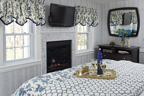 Quaint guest room with sunny windows, tv, gas fireplace, bureau and mirror and bed topped with tray of wine