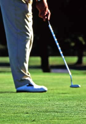 Bottom half of a man on the golf course green putting a ball