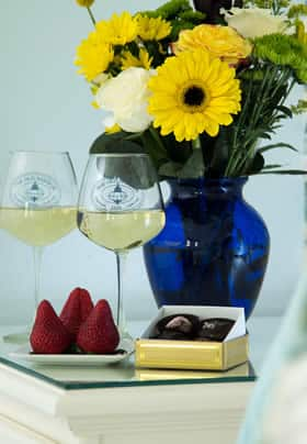 Two wine glasses filled with white wine next to chocolate, red strawberries and a blue vase of fresh yellow flowers