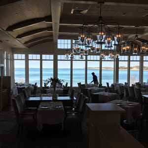 Elegant restaurant dining area with a wall of windows overlooking the blue ocean